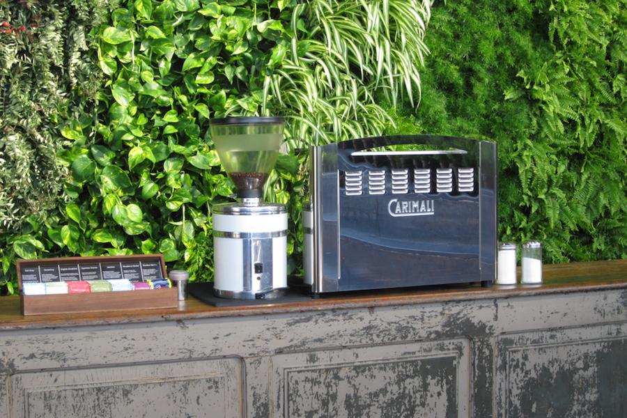 Espressomaschine vor vertikalem Beet auf dem Messestand.